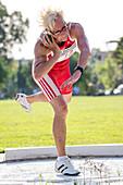 Fit older female athlete throws shot put