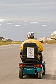 An Inuit man in a mobility scooter