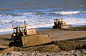 Bulldozers rebuilding beach
