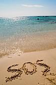 SOS written on a deserted beach