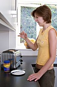 Woman burning her hand on a toaster