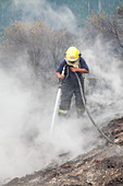 Firefighter tackling wildfire