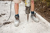 A builder using a jack hammer