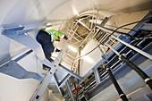An engineer climbs a wind turbine