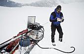Glaciologist drilling on a glacier
