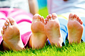 Children sitting on grass with bare feet