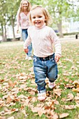 Young girl running in the leaves