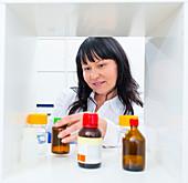 Pharmacist taking a bottle from a shelf