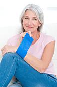Woman putting bandage on wrist