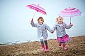 Two girls on beach holding umbrellas