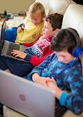 Three boys using laptops sitting on sofa