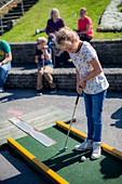 Girl playing mini golf