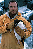 Researcher with adelie penguin