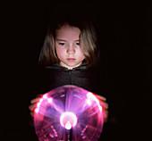 Girl touching a plasma globe