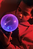 Boy touching a plasma globe