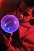 Boy touching a plasma globe