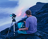 Man taking photographs of a lava flow
