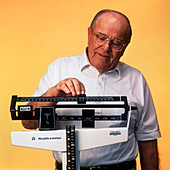 Elderly man standing on a weighing scale