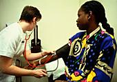 Nurse taking blood pressure of a female patient