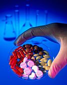 Gloved hand holding a dish of capsules & pills