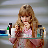 Child danger: young girl finds pills on a shelf