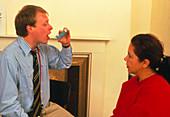 Doctor demonstrates inhaler to asthma patient