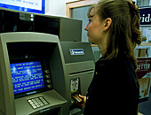 Woman has eye iris scanned at a bank cash machine