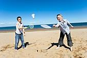 Boys playing badminton on a beach