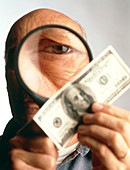 Man examines banknote with magnifying glass