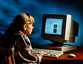 Young girl accessing internet from home computer