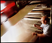 Worker checks the quality of film used in flooring