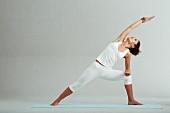 Gestreckter seitlicher Winkel, Schritt 1: Arm auf Oberschenkel ablegen, hinterer Arm über das Ohr nach oben strecken (Power-Yoga)