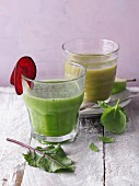 Two green smoothies garnished with beetroot and basil