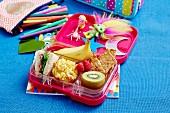 Pausenbox mit Banane, Kiwi, Gemüsemuffin, Sandwich und Himbeeren