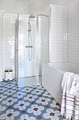 Badezimmerecke mit Badewanne und verglastem Duschbereich vor weiss gefliester Wand, am Boden Zementfliesen mit Blumenmotiv