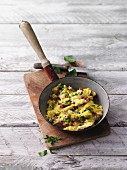 Herb scrambled egg with diced bacon in a pan