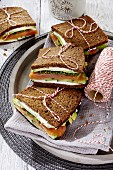 Black bread sandwiches with goat's cheese, smoked salmon and avocado