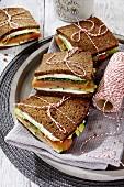 Schwarzbrot-Sandwiches mit Ziegenkäse, Räucherlachs und Avocado