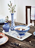 A tea cup, sugar candy and a blue and white table decoration