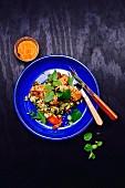 Couscoussalat mit Paprika, Möhren, Zucchini, Minze, Teriyaki-Hähnchen und Sesam, dazu Ajvar