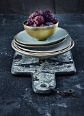 Frozen blackberries in a golden bowl on a stack of plates and a marble board