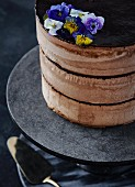 Chocolate cake with chocolate cream and edible flowers