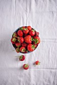 A bowl of fresh strawberries on a white tablecloth
