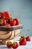 Strawberries in a wooden basket and on a white tablecloth