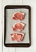Three raw pork chops on a baking tray