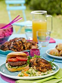 A burger and grilled chicken legs on a garden table