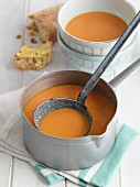 Tomato and mascarpone soup in a pan with soup bowls