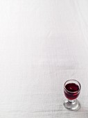 A glass of red wine on a white surface