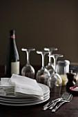 Tellerstapel, Stoffservietten, Weingläser, Weinflasche und Gewürze auf Holztisch