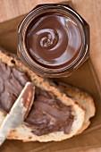 Schokoladenaufstrich im Glas und auf Brot